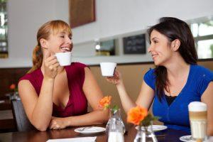 Zwei lachende Frauen im Café trinken Espresso